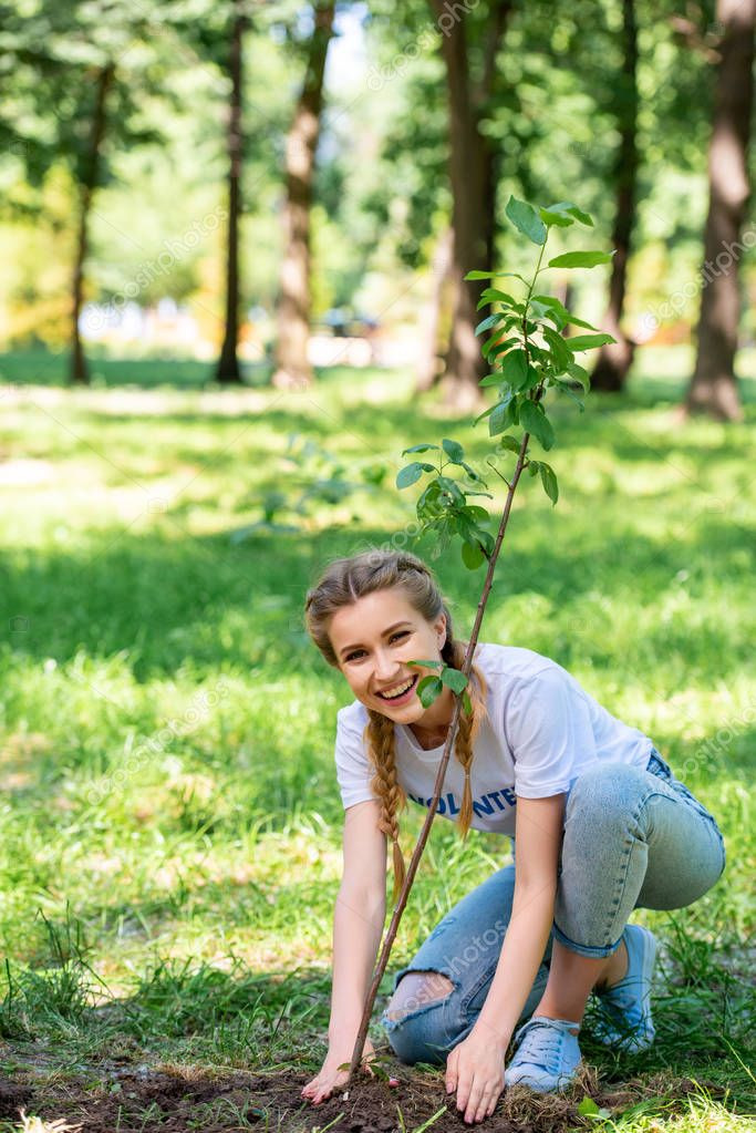 smiling beautiful volunteer planting new tree in park