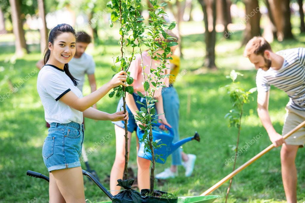 young happy friends planting new trees in park together