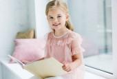imádnivaló gyermek, tartja a könyvet, és mosolyogva kamera ülve, ablakpárkányon