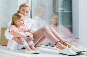 schöne, glückliche Mutter und Tochter sitzen zusammen auf der Fensterbank