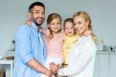 šťastná rodina s dvěma dětmi rozkošný úsměv na kameru společně doma