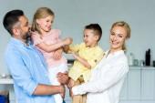 šťastní rodiče nesoucí rozkošné malé děti doma