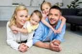 Fényképek boldog családi feküdt a szőnyegen, és mosolyogva kamera otthon