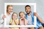 Fotografie glückliche Familie hält Rahmen und lächelt in die Kamera