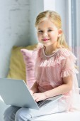 Photo adorable child using laptop and smiling at camera at home