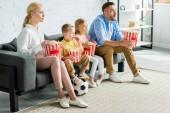 rodina s fotbalovým míčem sedí na gauči, jíst popcorn a koukal doma