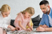 Fotografie parents with cute little daughter playing with puzzle pieces at home