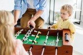 Photo cropped shot of father with cute little kids playing table football at home