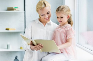 beautiful happy mother and daughter reading book together at home