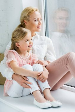 beautiful happy mother and daughter sitting together on windowsill and looking at window
