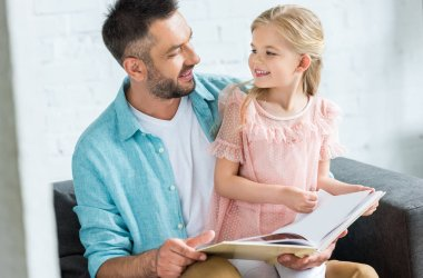 happy father and daughter smiling each other while reading book together at home