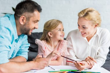 happy parents and cute little daughter drawing with colored pencils together at home