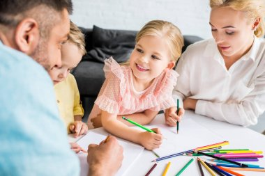 happy family with two children drawing with colored pencils at home