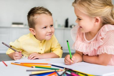 Adorable kids smiling each other while drawing with colored pencils together stock vector