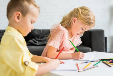 adorable little kids drawing with colored pencils at home