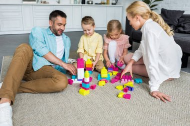 happy family with two little children playing with colorful blocks at home