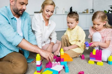 happy parents with cute little children playing with colorful blocks at home