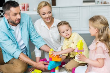 parents with adorable little kids playing with colorful blocks at home