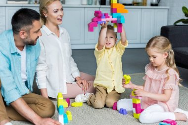 happy family playing with colorful blocks at home