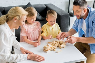happy family with two kids playing with wooden blocks at home