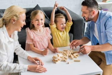 happy family playing with wooden blocks at home