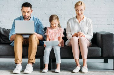 family with one child sitting on couch and using digital devices