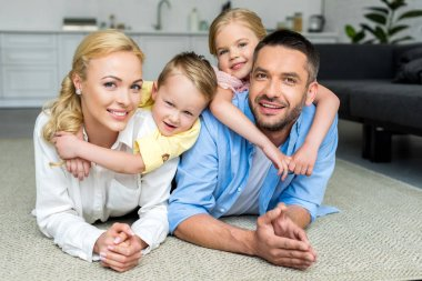 happy family lying on carpet and smiling at camera at home