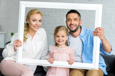 happy parents with adorable little daughter holding white frame and smiling at camera