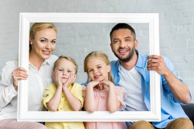 happy family holding frame and smiling at camera