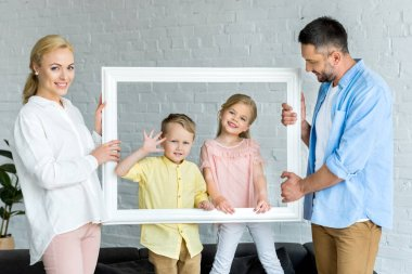 happy parents holding frame and cute little kids smiling at camera
