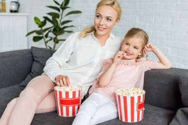 beautiful smiling mother and daughter eating popcorn and looking away at home
