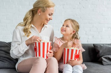 happy mother and daughter smiling each other while eating popcorn at home