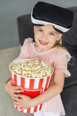 beautiful child in virtual reality headset holding box with popcorn and smiling at camera