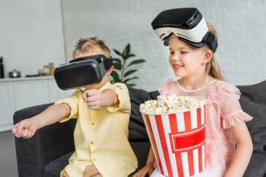 adorable kids using virtual reality headsets and eating popcorn at home