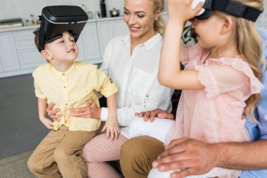 cropped shot of parents playing with kids using virtual reality headsets at home