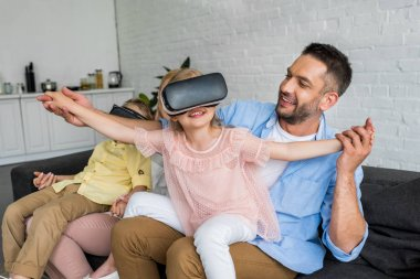 happy parents playing with kids using virtual reality headsets at home