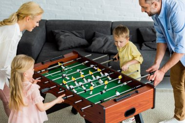 high angle view of happy family with two children playing table football together at home
