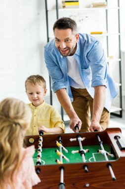 happy father with two adorable kids playing table football at home