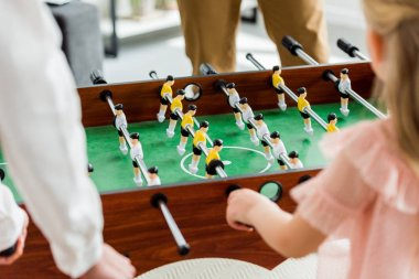 cropped shot of family playing table football together at home