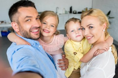 happy family with two kids hugging and smiling at camera at home