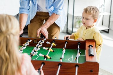 cropped shot of father with cute little kids playing table football at home