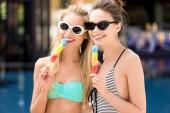 Fényképek boldog fiatal női fürdőruha-bikini ölelni, popsicles látszó-on fényképezőgép, medence közeli portréja