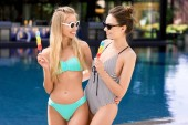 Fényképek happy young embracing women in swimsuit and bikini with popsicles at poolside