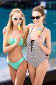 Fényképek szép fiatal női fürdőruha-bikini eszik popsicles medence átfogó