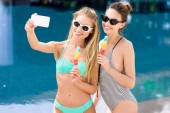 Fényképek fürdőruha-bikini véve selfie, popsicles medence boldog fiatal nők