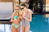 Fényképek fürdőruha-bikini popsicles eszik, és használ smartphone medence boldog fiatal nők
