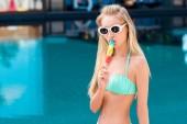 Fényképek gyönyörű fiatal nő a bikini és a vintage napszemüveg eszik színes popsicle medence