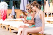 Fényképek beautiful young women in swimsuit and bikini with popsicles using smartphone while sitting on sun lounger at poolside