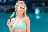 Fényképek gyönyörű fiatal nő a bikini és a vintage napszemüveg színes popsicle medence