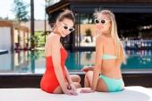 zadní pohled atraktivních mladých žen, odpočinek na lehátku u bazénu a při pohledu na fotoaparát